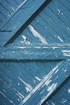 peeling blue paint on a barn door