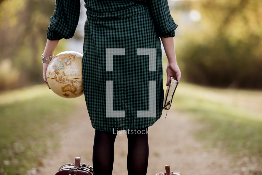 a woman holding a Bible and globe