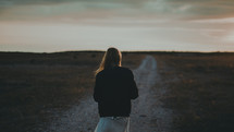 a woman with her back to the camera standing on a gravel road at dusk