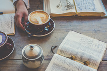 woman drinking a cappuccino and reading a Bible