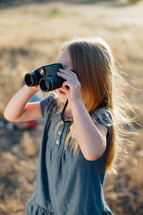 a girl child looking through binoculars
