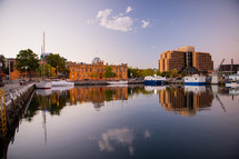 Reflections of boats and buildings in the bay water.