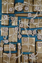 Advent calendar with twenty four golden presents on teal wood
