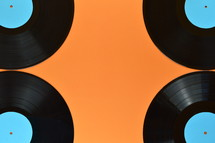four old black vinyl records with blank cyan labels on orange background