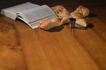 open Bible, cross shaped bread, and cup of communion wine