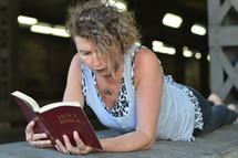 a punk woman sitting under a bridge reading a Bible