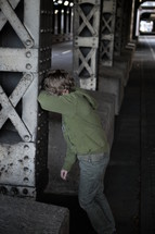 a scared and lost little boy standing at a steel upright in a dark underground covering his face