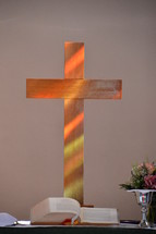 sunlight falling through a stained-glass window and illuminating a wooden cross at the altar.