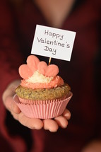 Woman offering a cupcake with pink hearts and a sign saying HAPPY VALENTINE'S DAY.