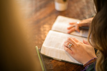 a woman reading a Bible at a table