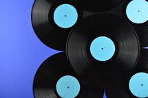 pile of old black vinyl records with blank cyan labels on blue background
