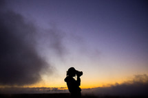 silhouette of woman with a camera taking a picture at dusk