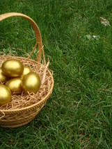 Basket of gold Easter eggs in the grass.