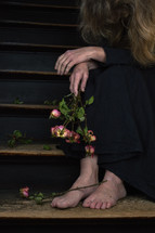 a woman with a bouquet of dead roses