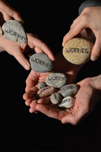 People are giving their worries in the symbol of stones into the hands of Jesus.