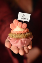 Woman offering a cupcake with pink hearts and a sign saying JE T'AIME, which means: I LOVE YOU.