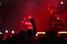 silhouette of a raised hand during a worship service