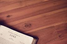 BIble on a wood floor opened to Luke