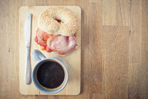bacon, bagel, coffee, and knife on a wood plate