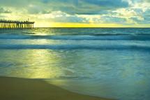 waves on the beach near a pier
