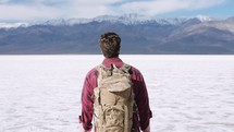 a man hiking through the desert alone