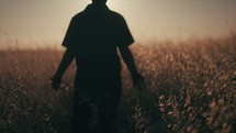 Young man walking through a field.  Standing in a field during Sunset.