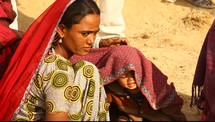 mother covering her child with a blanket in the desert