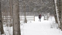 woman walking in falling snow on a farm