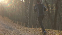 man running along a path in fall