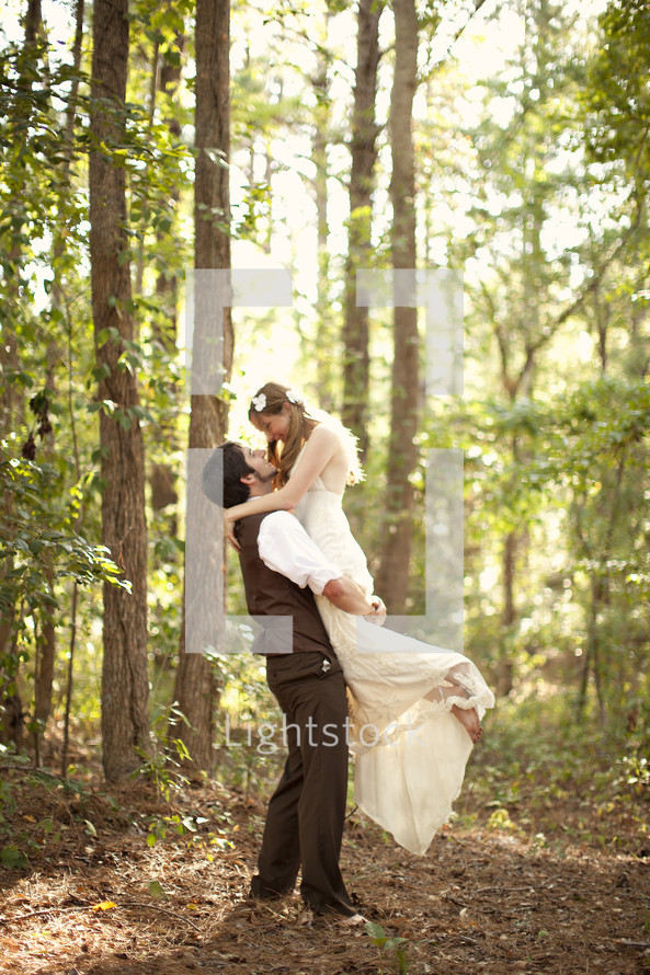 Groom holding bride in arms outdoors