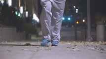 feet of a man walking down a sidewalk alone at night