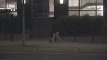 a young man walking alone on a sidewalk at night