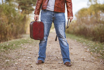 a man standing holding a suitcase and Bible