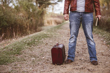 a man standing with a suitcase and Bible