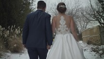 bride and groom walking hand in hand outdoors