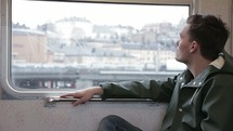 man looking out a window of a subway train