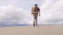 a man hiking alone through the desert