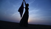 woman with a scarf dancing in a desert at sunset