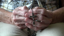 elderly woman praying with a rosary