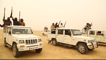 men with rifles riding in trucks through a desert