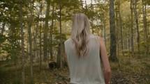a woman walking through a forest