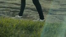 legs of a man walking on rocky terrain