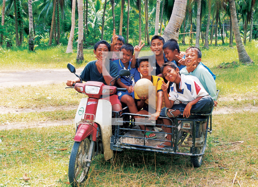 Eight kids in on a motorbike and side car carriage