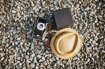 straw hat, camera, and canteen on gravel
