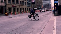 man riding a bike across a city street and people using a crosswalk