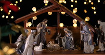 Jesus Christ Nativity scene with atmospheric lights near Christmas tree. Christmas scene. Dolly shot 4k