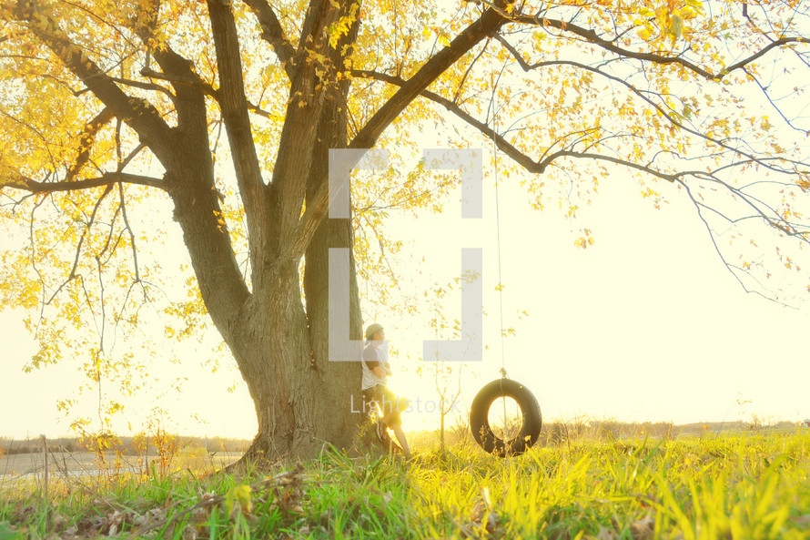 A person leaning against a tree near a tire swing.
