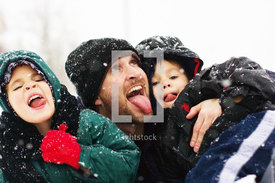A father and his two sons playing in snow