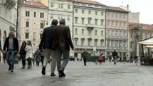 people walking in a courtyard in Trieste, Italy