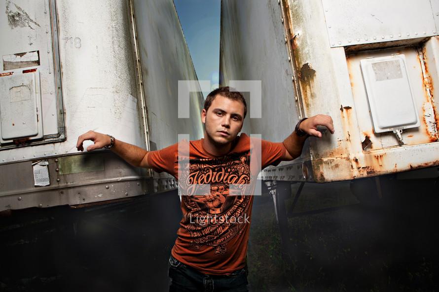 boy standing between two trailers
